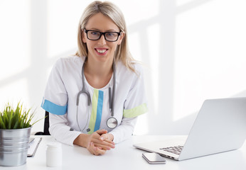 Female doctor sitting at the desk in the office