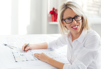 Young female architect sitting at her desk in the office