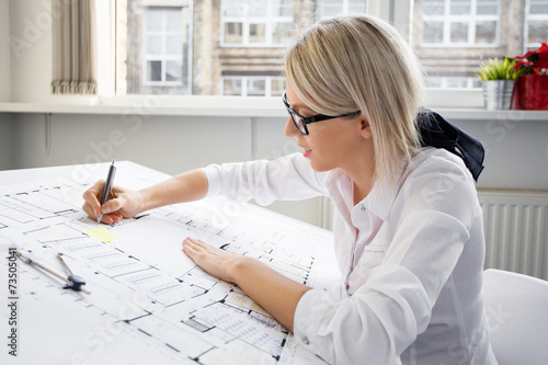 Young female architect working on blueprint - 73505041