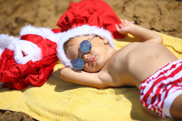baby Santa Claus with gifts on the beach