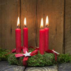 Adventskranz mit vier roten brennenden Kerzen
