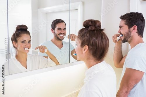 Young couple brushing their teeth - 73508429