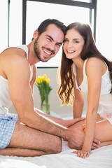 Young couple smiling at camera in bed