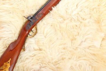 Close up of hunting gun on a sheep fur.