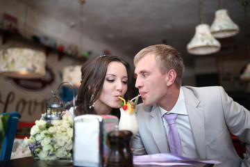 Жених с невестой пьют вместе коктейль