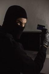 Hacker using debit card and laptop