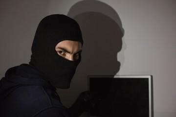 Hacker in balaclava hacking laptop while looking at camera