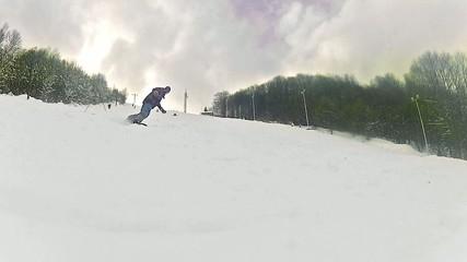 Snowboard spraying snow into camera