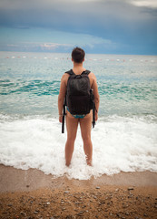 man wearing tourist backpack standing on sea shore