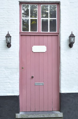 Pink door in a white stone wall
