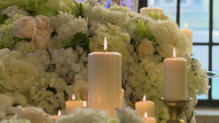 Lighted candles on backdrop of white flowers