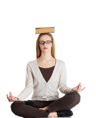 Woman sitting cross-legged holding book on head