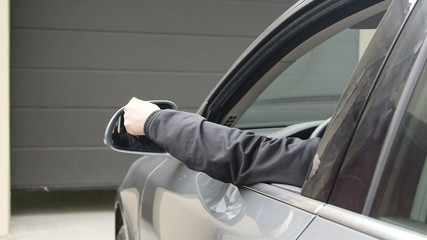 driver  holding remote control to open automatic garage door