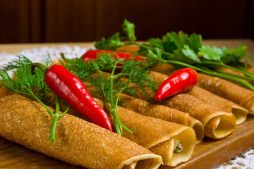 pancakes, rolled on a wooden board with herbs and hot pepper
