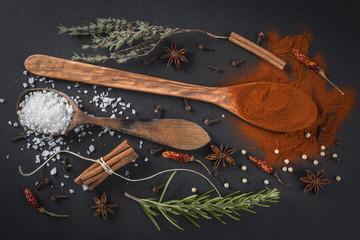 Cucharas de madera con especias y hierbas aromáticas en cocina