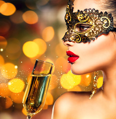 Sexy model woman with glass of champagne wearing mask
