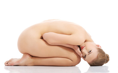 Side view nude woman curled up on the floor