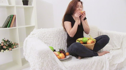 Girl sitting on white sofa and eating fruits
