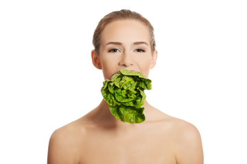 Portrait of nude woman eating lettuce