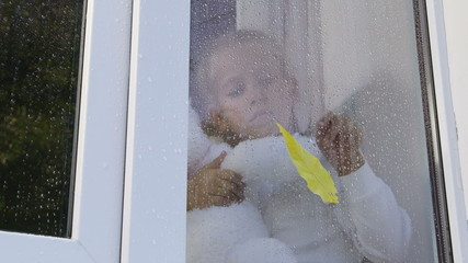 Child draws on the window pane in raindrops with yellow leaf
