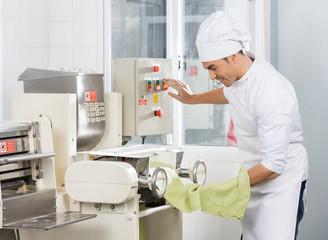 Smiling Chef Operating Spaghetti Pasta Machine
