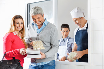 Couple Holding Pasta Packets By Chefs At Window