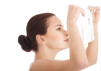 Woman applying cosmetic facial mask