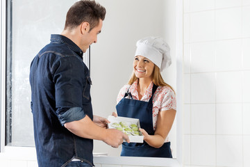 Happy Chef Selling Uncooked Ravioli Pasta Packet To Man