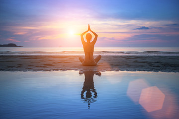 Woman practicing yoga on beach at surrealistic sunset.