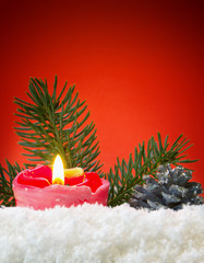 Advent candle isolated on red background.