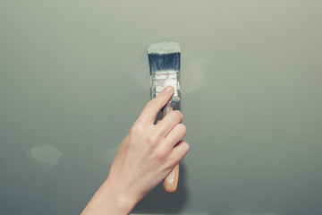 Hand of young woman painting a wall