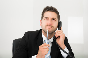 Thoughtful Businessman Looking Up While Using Telephone