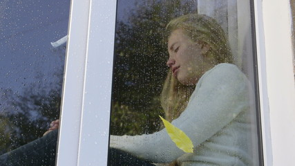 Teenage girl at window crying in the rain