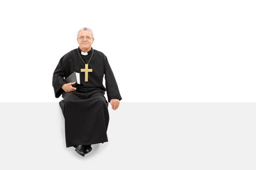 Mature priest sitting on a blank panel