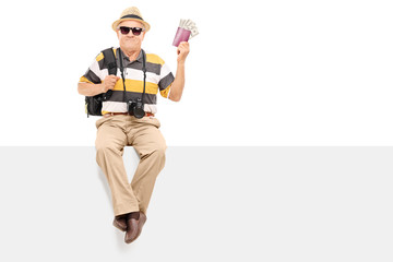 Mature tourist holding passport with money