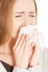 Close up woman holding tissue sneezing