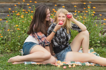 Blonde and brunette holding red apples