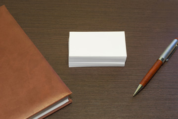 Blank business card with a diary and pen