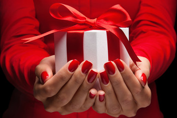 Gift with red bow in female hands
