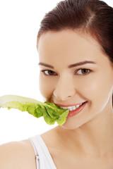 Portrait of a woman eating lettuce leaf