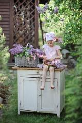 Little beautiful girl in spring garden making lilac wreath