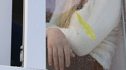 girl sitting behind window glass with rain drops in autumn