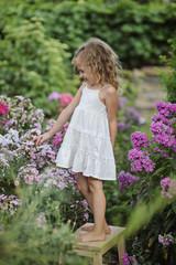 Beautiful little girl in summer blossom garden