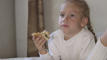 Little girl eating pizza and watching TV on the bed at home
