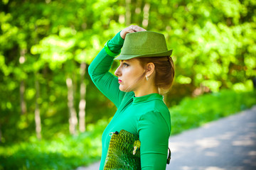 Beautiful girl in a green dress and hat