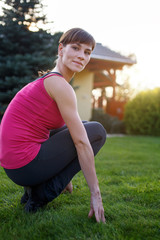 Young woman squat in sportswear during sunset