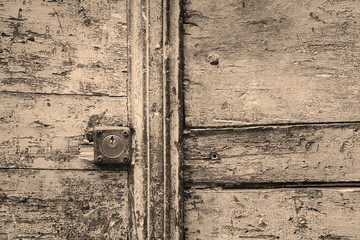 rusty keyhole in a wooden door in black and white