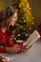 Young woman with cup of hot chocolate reading book