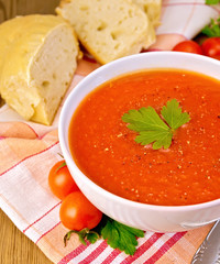 Tomato soup in bowl with bread on napkin