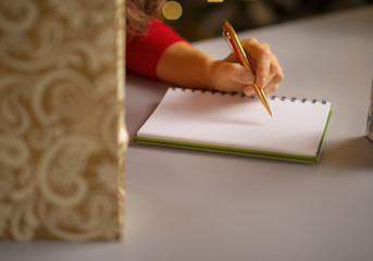 Closeup on young woman writing in notebook list of purchasings